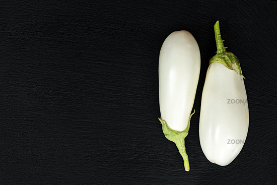 White eggplant on a black stone surface. Top view. Copy space.