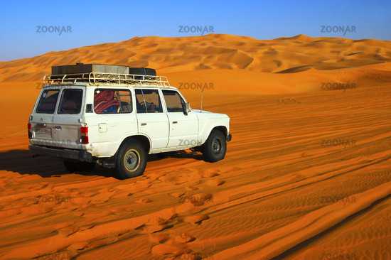 off-road vehicle on a desert road through sand dunes in the Sahara