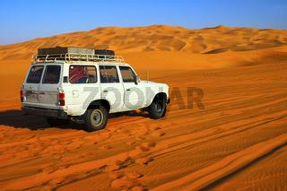 Geländewagen auf einer Wüstenpiste durch Sanddünen in der Sahara