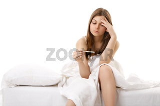 The afflicted girl sits in bed and sees result of the test for pregnancy