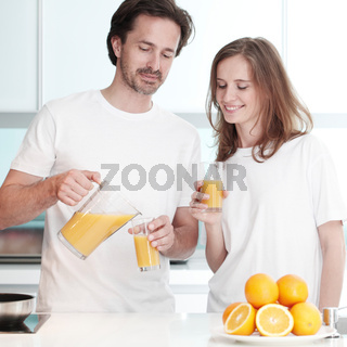 Couple with juice in the kitchen