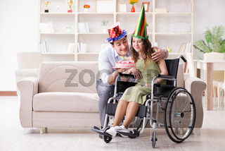Young family celebrating birthday with disabled person