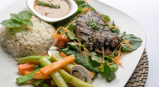 Beef filet steak served with rice, vegetables and mushroom