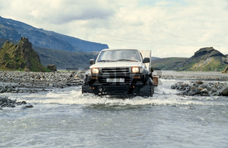 Car pulling trailer and crossing river in Iceland
