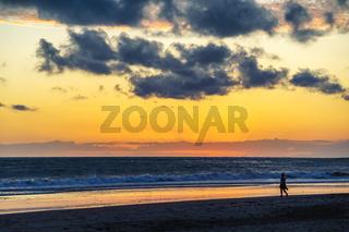 Junge Frau geht bei Sonnenuntergang am Strand entlang