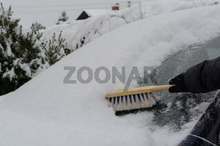Mit Schneebesen kehrt Autofahrerin die verschneite Windschutzscheibe ab - Nahaufnahme