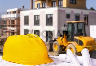 Helm mit Bauplänen und Baustelle
