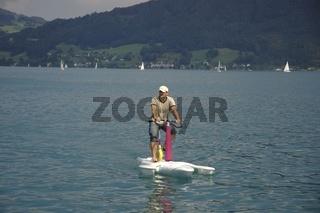 Ein Mann fährt mit einem Wasserfahrrad am Attersee