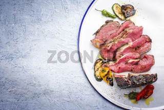 Barbecue dry aged wagyu sliced roast beef steak with vegetable as close-up on a white plate