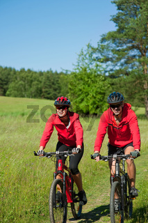 Young couple with mountine bike in spring nature