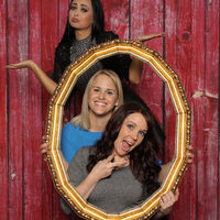 3 girls look through a golden frame and silly around