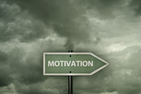 the word motivation on sign in front of cloudy sky