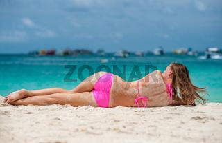 Woman wearing pink bikini laying on beach