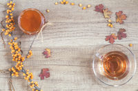 Autumn healthy hot drink concept. Branch of common sea buckthorn with berry, cup of tea, jar of jam on light wooden background