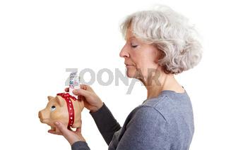 Seniorin steckt Geld in Sparschwein