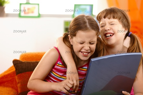Cute girl friends laughing at laptop