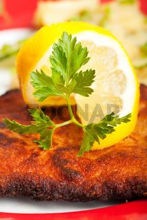 Nahaufnahme einer Zitronenscheibe auf einem Wiener Schnitzel