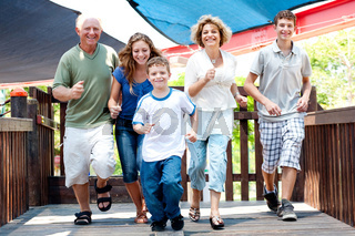 Family of five running on the wooden bridge