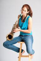 Beautiful young woman saxophone player