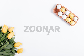 Top view of Easter eggs and yellow tulips on a white table