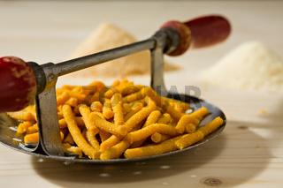 Closeup of Passatelli original Italian pasta on its tool