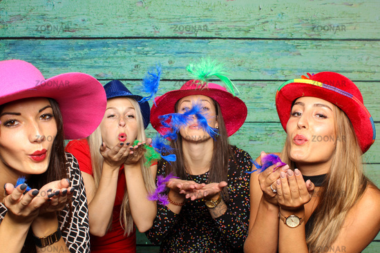 women blow with hats colorful feathers from hands - fun with the photo box