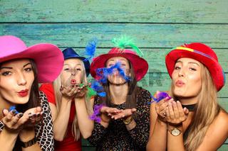 frauen mit hüte pusten bunte federn aus den händen- fotobox party