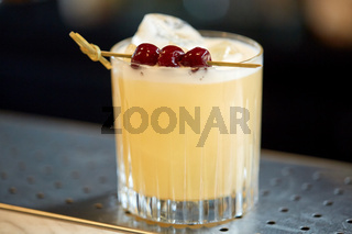 glass of cocktail with cherries at bar