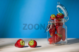Strawberries on a table and a glass jar full of strawberries