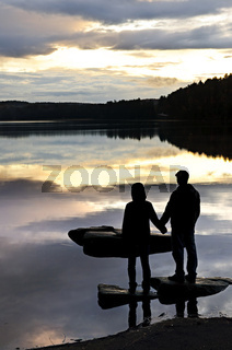 Silhouette of people watching sunset at lake