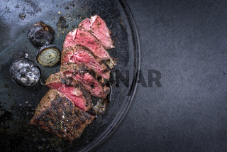 Barbecue dry aged caveman wagyu chateaubriand steak with onions sliced as close-up on a board