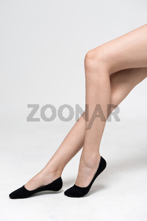 Female legs in socks. Isolated on a Grey  background.