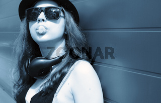 Cute girl hipster in a light hat and sunglasses on a summer day