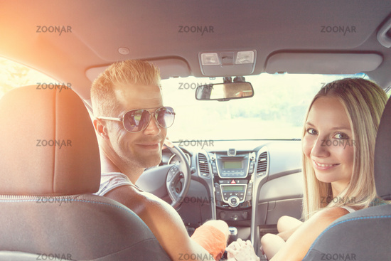 Young happy people enjoying a roadtrip in the car
