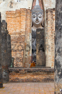Wat Si Chum temple with tourists and monk Sukhothai Thailand