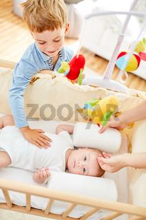 Bruder streichelt neugeborenes Baby