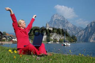 Blonde Frau im Anzug entspannt sich am Traunsee von der Arbeit am PC