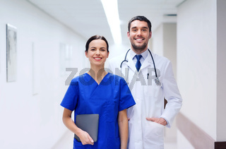 smiling doctor in white coat and nurse at hospital