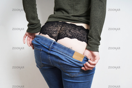 rear view of young woman undressing wearing black lace panties underneath blue jeans