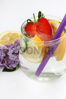 Detox flavored water with lemon, cucumber and  strawberry on white background with lilac and wood de