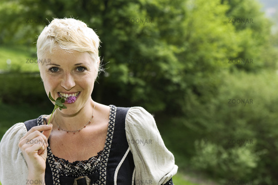 young woman gathers wild herbs