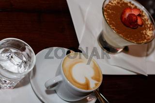 fein zubereiteter Kaffee mit Milchschaum und süsser Nachspeise