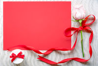 Pink rose with a gift and red paper sheet