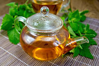 Tea with mint in glass teapot on wooden board