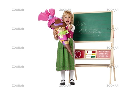 Girl on first school day stands beside chalk board