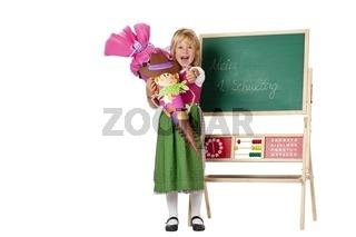 Mädchen mit Schultüte steht am 1. Schultag vor Tafel und zeigt D