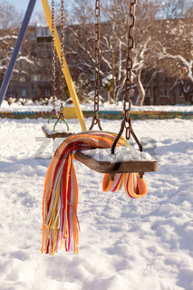 Empty swing with snow and checkered scarf