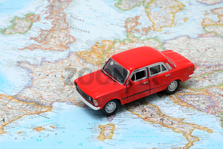 Tiny red car model on the map of europe