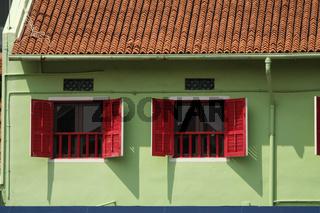 Roter Fensterladen an einem grünen Haus in Singapur