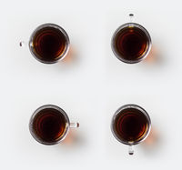 Top view of glass cup of hot black tea on white background desk for mockup